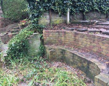 overgroeide gebroken muur en ronde bank
